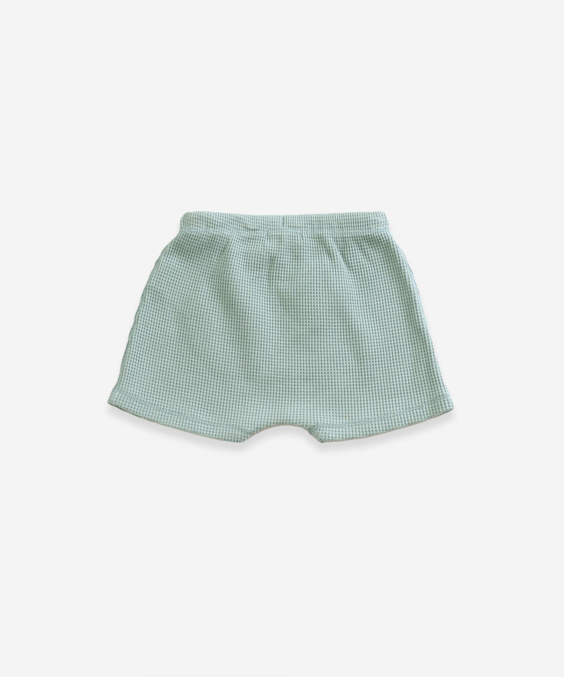 Pantalón corto de algodón orgánico con bolsillo estilo canguro | Weaving