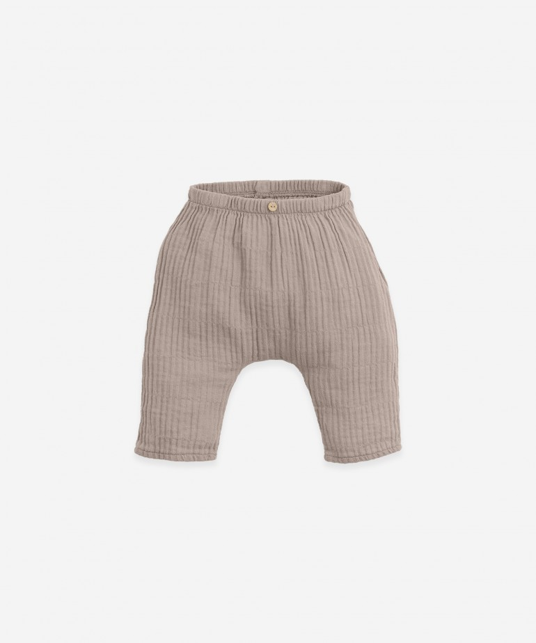 Woven trousers with decorative button